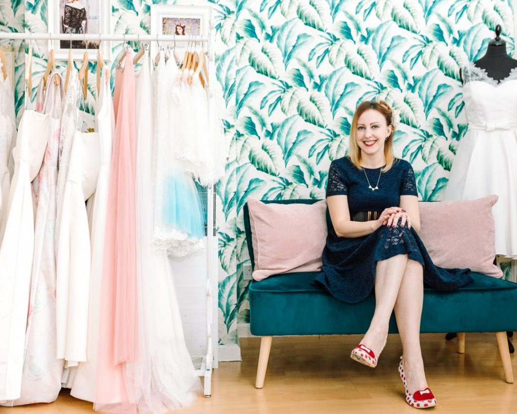 Louise Rose sits between pink cushions on a teal sofa in her bridal boutique in Reading, UK. To the left is a rail of her bespoke wedding dresses, and behind her is green patterned wallpaper. Branding photography by carlawatkins.com