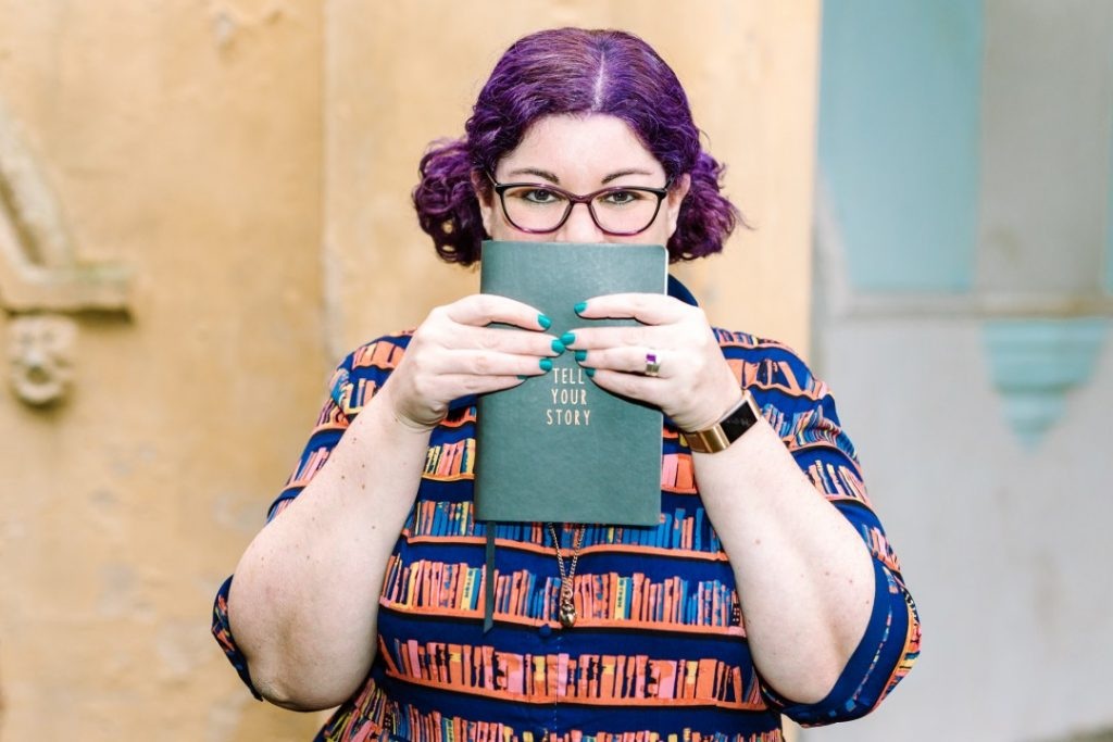 "Sarah Wayte has curly purple hair in bunches, is wearing a book-print dress and glasses, and holding a notebook up to her face which says ""Tell Your Story"". She's standing against an old building which is partly beige and partly blue and grey. Branding photography by carlawatkins.com"