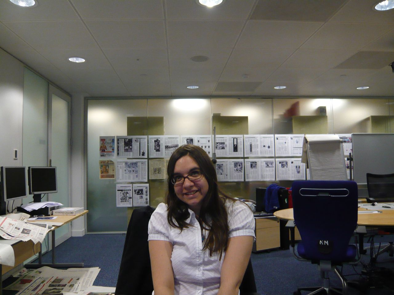 Carla sitting at a desk in a room full of newspaper layouts. She has medium length dark hair so you can tell it's 2008! | carlawatkins.com