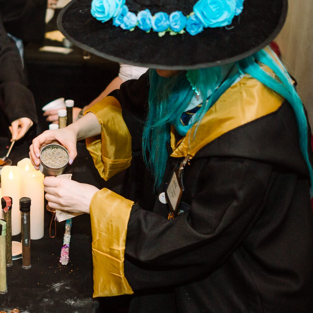 A witch (or wizard) measuring potion ingredients (possibly tea).
