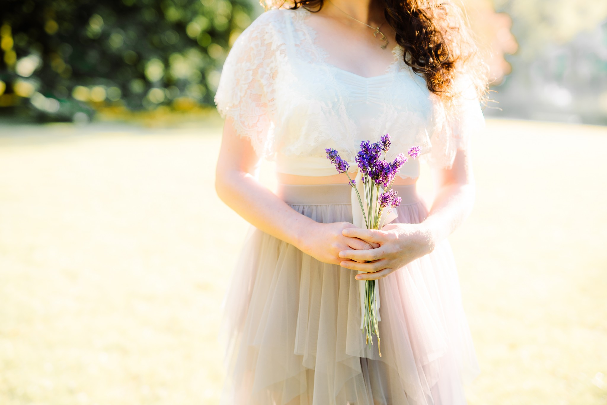 A fine art fairytale image of a girl with dark curly hair, wearing a chiffon skirt and lace top, holding some lavender in front of her