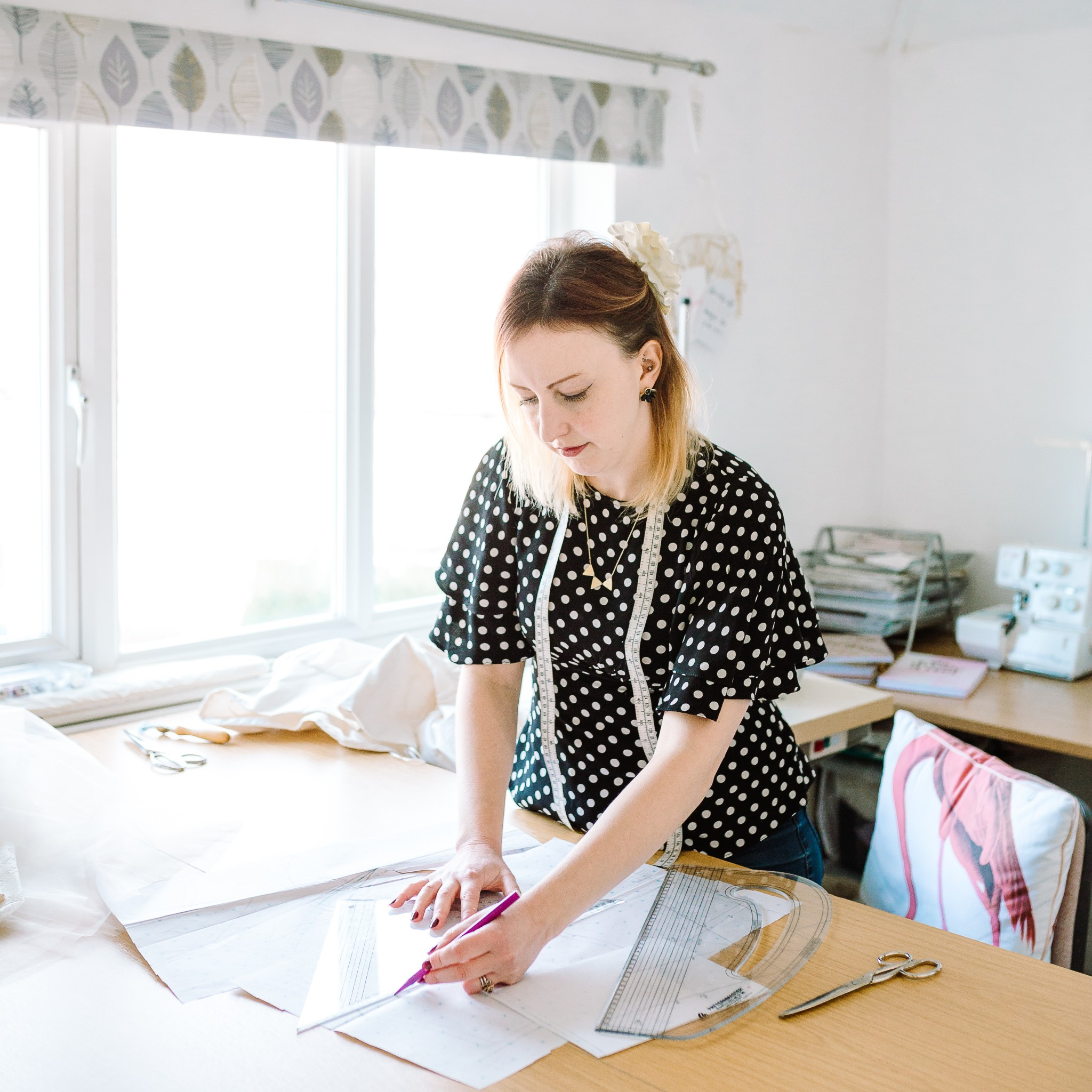 A photo from a personal branding photography session with Louise Rose Couture. Louise is standing at her pattern cutting table, measuring a sewing pattern to cut out. She's wearing a polka dot top and has a tape measure around her neck, and her overlocker is visible in the background.