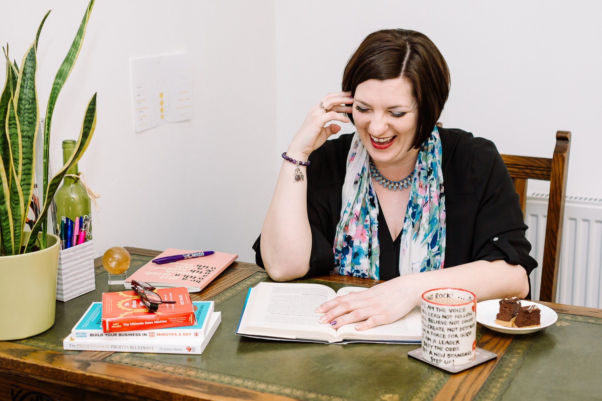 A shot from a personal branding photography session with One of Many life and business coach Tabitha Pascoe, who sits at her desk with an open book, smiling.
