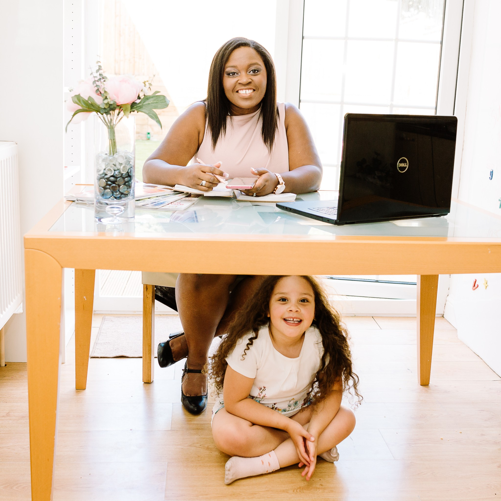 An image from a personal branding shoot with property sourcer Jasmine Doidge, who is sitting at her desk behind her laptop, with her daughter sitting under the desk