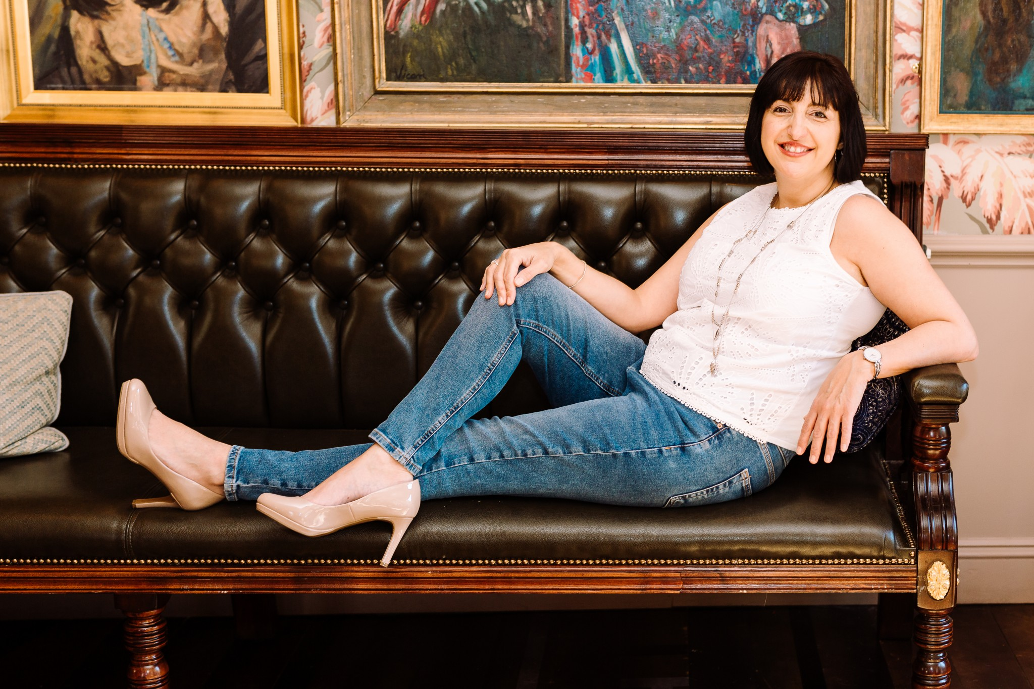 A woman sits on a wooden sofa, wearing jeans and high heels.